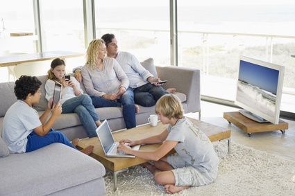Couple watching television set while their children busy in diff