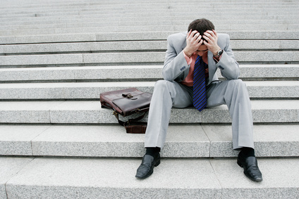 Depressed businessman sitting on the stairs.
